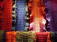 Susan Neal an outstanding weaver. Wool scarves woven, felted (fulled), then cut to remove portions of the weave to creating a pattern of hole, texture and fringe.