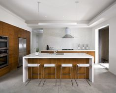 Wood cabinetry + high gloss white create an understated #midcentury #modern #kitchen