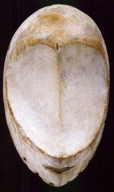 "Image courtesy Fowler Museum at UCLA, Los Angeles, CA, USA (#X2007.21.63). A very rare idumu mask without eyes.It has been suggested that Bwami members attached cowrie shells to serve as eyes, but this seems unlikely since the kaolin on these examples is even, ...the masks illustrate the saying ""Big-One of the men's house, the guardian, has no eyes"" ,Although this important high-level Bwami member does not see with his eyes, he sees with his heart and guards the affairs of the community."