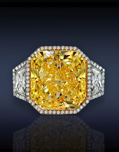 Three Stones Diamond Solitaire, Featuring: GIA Certified 13.00 Ct Fancy Intense Yellow, VS1, Radiant Cut Diamond, Flanked by 1.43 Ct Trapezoid Shape Diamonds (2 Side Stones), Surrounded by Pave' Set 1.25 Ct Round Brilliant Cut Diamonds, Mounted in Platinum & 18K Yellow Gold.
