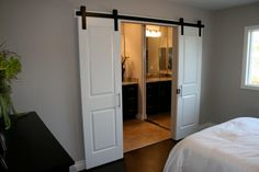 As seen on HGTV's Flip or Flop, white sliding doors have been installed in a contemporary master bedroom creating a grand entrance into the bathroom. A black accent above the doors adds an edgy touch.