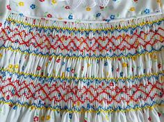 Ideal pequeño vestido para una fiesta u ocasión especial. Delicadas flores en azul, rojo y amarillo. Una cortesía de collar encaje este vestido maravillosamente y su acabado apagado con cinta amarilla cosida justo por encima de la línea del dobladillo.