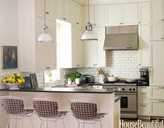 Designer and homeowner Kim Fiscus likes to mix in a few modern pieces with her antiques, such as the Bertoia stools in the kitchen.   - HouseBeautiful.com