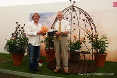 David Domoney presents rose breeder Chris Warner with a commemorative vase, as Rosa 'Scent from Heaven' is unveiled as the winner of the prestigious title of 'Rose of the Year 2017'. David Domoney and Chris Warner are pictured inside The Festival of Roses Marquee, at the RHS Hampton Court Palace Flower Show 2016.
