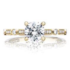 Round-cut diamond ring by Tacori featuring bezel-set brilliant round diamonds enveloped in circular and rectangular yellow gold baskets.