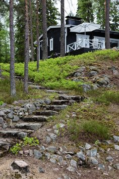 hand-hewn stone steps lead to a cottage painted black with white trim