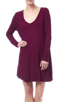 Raspberry-colored Claire Mini Dress from Knot Sisters. Features a ribbed texture long sleeves hip pockets and a swingy silhouette. Finished with front seam detailing and raw edges on sleeves and hem.  Ribbed V-Neck Dress by Knot Sisters. Clothing - Dresses - Long Sleeve Clothing - Dresses - Casual New York