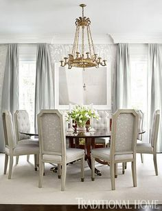 An antique table and chandelier anchor this glamorous dining room that shimmers in silver. - Traditional Home ® / Photo: Emily Jenkins Followill / Design: Bradshaw Orrell
