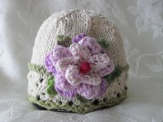 This knitted Easter baby hat is made with soft cotton ivory yarn for your little princess. The scalloped edge is in pastel green to match the leaves surrounding the Easter flower. The three layered flower is in hues of lavender.! I can also knit a matching diaper with flowers to match.