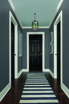 Stark white and jarring gray walls paint a handsome picture in a well-designed hallway. Shown here: Nautica at Home's Rivet Gray.
