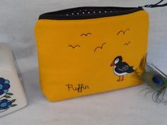 Product: Cosmetic Bag  ·Purse/Cosmetic bag (22 x 16 x 3cm) made using bright canvas fabric ·Flat bottom so that it stands alone ·Puffin quirky free motion embroidery appliqued design ·Lightly padded and lined with spotty fabric ·A beautifully made item ·Wrapped in shabby chic spotty cellophane  About the Artist  My name is Julie Filmer and I am a Textile Artist specialising in personalised fabric gifts. The Peacock Emporium is a shop full of pieces lovingly made in my Norfolk studio. I g...