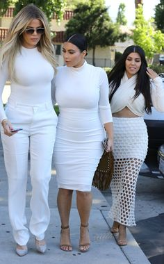 Khloé chose white trousers, a tight long-sleeved t-shirt, suede pumps, and gold-rimmed aviators. Meanwhile, Kim opted for a body-hugging sheath dress. She completed her look with ankle-strap sandals that were similar to Kourtney's. Kourtney opted a crop top and a mesh skirt.