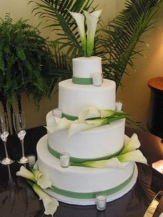 Large fresh calla lilies and votives create a pleasing display with palms and ferns behind. (803) 386-8806 www.VintageBakery.com
