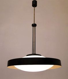 A large and very rare 1960s Italian space-age ceiling fixture by Stilnovo.   Beautifully proportioned, with circular opal glass inner shade, black steel outer ring, brass stem and three-rod black steel stem adornment, the components create a wonderful modernist form.  With a diameter of 56cm and a drop of 95cm, it is large enough to illuminate a wide area.  It is in excellent, rewired condition with minor wear and dulling to the brass commensurate with age.
