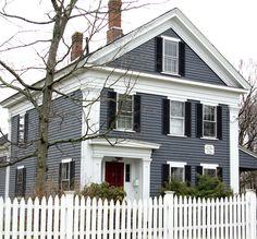 Dark gray/blue siding, white trim, red door, black shutters, white picket fence
