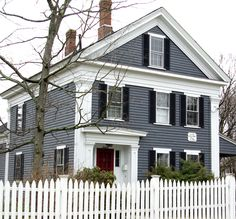 Dark gray/blue siding, white trim, red door, black shutters, white picket fence