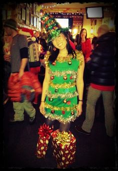 The finished Christmas tree costume. Bought the dress and hat, decorated the dress w mini ornaments, and made present feet from cardboard boxes, wrapping paper, and giant bows.