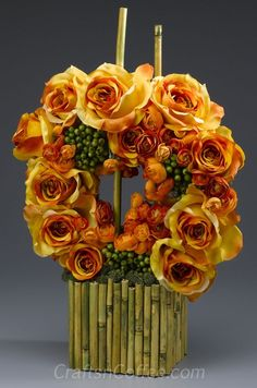 This is the prettiest centerpiece for fall, with beautiful orange roses and branches of bamboo.