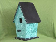 """This painted birdhouse is titled """"Nesting in Blue"""". It is a gorgeous shade of aqua, with darker aqua dots and swirls, also white dots. The roof is painted solid black. A row of white dots march up and down the gable ends. The perch is black with white dots, as is the base. 9"""" tall, 6"""" wide, 5"""" depth It is covered with a sealer, but I recommend indoor décor use only. In the interests of full disclosure, this was painted in November 2003, as noted on the bottom. It is not used, it has been…"""