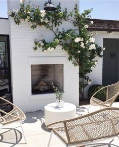 outdoor living space with white fireplace and flowering bush