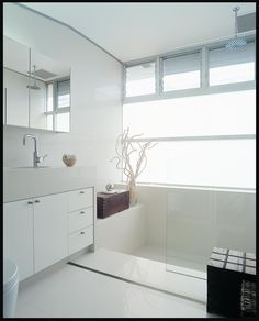 Minimalist white bathroom that blends glossy, oversize tiles, stainless steel accents and glass panes wonderfully.
