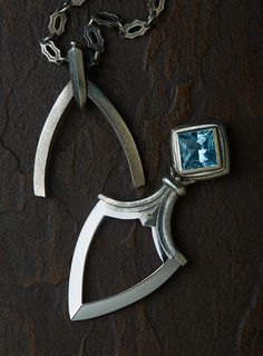 Female push dagger on a chain with a crystal.