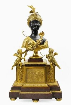 """La première pendule """"au nègre"""" qui soit datée fut livrée en 1784 pour Marie-Antoinette. Il est intéressant de noter qu'il ne s'agit pas d'un « nègre » mais d'une « négresse » dont plusieurs exemplaires sont connus. C'est l'œuvre de deux horlogers du roi, FURET et GAUDRON. La boite de cette pendule est entièrement en bronze ciselé et doré et seul la peau de la nubienne est en bronze patiné ce qui renforce le contraste. Epoque Louis XVI. Courtesy of Delorme Collin du Bocage"""