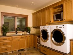 This spacious laundry room is filled with wood cabinets and drawers for plenty of storage.