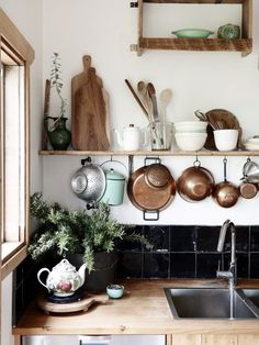 Hanging copper pots and pans on an open shelf above the sink.