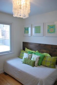 Pretty spare bedroom. Cheap white quilt, mix and match pillows, scrapbook paper framed in white