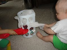 Using a $1 plastic bag dispenser (from Target), I made Baby H (8 months old) a new game. I filled the dispenser with silk scarves and inv...