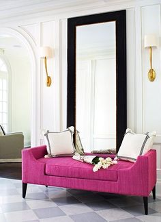 The mirror behind the fuchsia loveseat adds an elegant finishing touch to this living room.