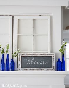Spring Mantel with chalkboard and blue bottles, by Lilypad Cottage