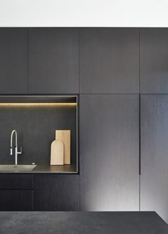 M House is a minimalist house located in Melbourne, Australia, designed by DKO. The kitchen space features blacked out custom cabinetry with a black kitchen island that allows for seating and serving. (3)