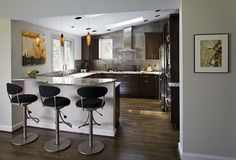 Wet bar with easy kitchen access and hanging lights