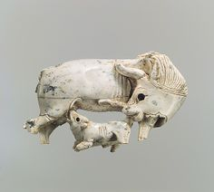 Ivory Plaque fragment with a cow and suckling calf. Neo-Assyrian Date: ca. 9th–8th C. BCE. Mesopotamia, Nimrud. 1.73 x 3.19 x 0.59 in
