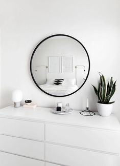 Round mirror, white bedroom, use some greenery to bring it alive!