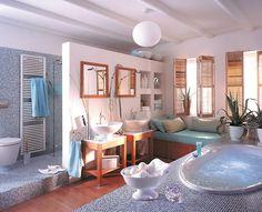 Wellness-Atmosphäre im Bad  Wellness für zu Hause: Der luxuriöse Whirlpool, eine geräumige Dusche hinter dem Raumteiler, eine gepolsterte Ruhebank und die Kombination aus Holz, blauem Mosaik und weißen Putzwänden erfreuen die Sinne. Besonders praktisch: Der Banksockel und die Nischen in der Leichtbauwand bieten ausreichend Platz für Badetücher und Utensilien.