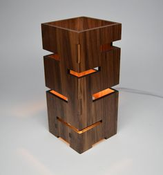 This handmade geometric lamp features multiple linear cut-aways from solid wood for an exciting light display when this piece is illuminated. The vertical grain of the wood contrasts the horizontal cutouts for a striking aesthetic look that is sure to please. Laser cut finger joints ensure solid craftsmanship and a product that is made to last. This lamp is stunning with and without the lights on! Available in solid Walnut, Cherry wood, or Maple. Size: 4 x 4 x 9. This has a 8 white or brown…