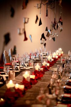 Um, let me count the ways I love this set-up. Drippy spooky shredded table cloth, the dark red napkins and the black bacara roses, feathers, eggplant orchids, broken mirrors, and dark spindly branches combined to create that spooky yet elegant hanging centerpiece! WOW.