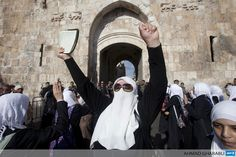 JERUSALEM : A Palestinian woman raises up a Koran, Islam's Holy Book, during a protest on September 4, 2013 after the Lion gate in Jerusalem was blocked by Israeli border guards. The entrance to al-Aqsa Mosque in Jerusalem's old city was temporary closed after disturbances due to the arrest of a firebrand Arab-Israeli Islamist preacher the day before. AFP PHOTO/AHMAD GHARABLI