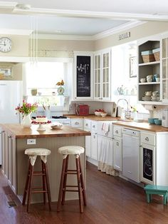Neutral blue and tan kitchen.  Light but not all white.  Black chalkboard keeps it from being too country.