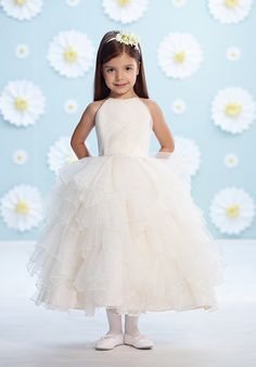 Sleeveless satin and tulle tea-length full A-line dress with mock halter neckline, satin bodice with directionally ruched tulle, large satin flower at back waist with center hand-beading, gathered multi-tiered tulle skirt.