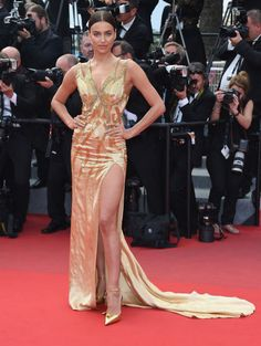 Bradley Cooper's rumored girlfriend continues to bring the heat in this gold Versace gown with an up-to-there slit.