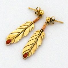 """ZAAMINI-GIIZIS (""""TOUCHES THE SUN""""): 21K yellow gold  and red gold eagle tail feather post-back earrings. Tips of eagle feathers are mounted with pear-shaped red coral cabochons."""