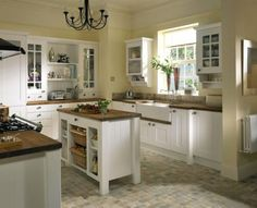 White cabinets, glass doors, kitchen island with  lots of storage. Great kitchen sink too