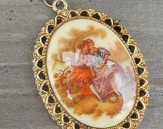 Vintage Fraganard pendant necklace, oval transferware, French Baroque style courting couple, gold tone filagree setting & chain, 1960's era