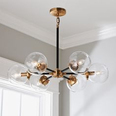 This beautiful mid-century modern chandelier features clear glass globe shades and a mixed metal frame in Matte Black and Antique Gold.