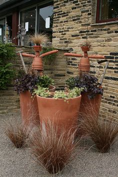 Minus the crazy terra cotta men these pots look great with purple fountain grass and pebbles or crushed stone. Great southwestern look.