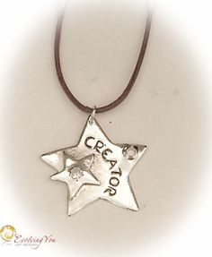 """Handcrafted fine silver pendant with a 'Creator' medallion on a purple leather cord (length 60cm) . No 239. The word """"CREATOR"""" is handcarved. The big star measures 30 mm in diameter and has 1 little star coming with it measuring 14 mm in diameter. The 2 embedded white cubic zirconia stones measures 3 and 4 mm in diameter. The front is high polished and the back has a matt finish.   It reminds you of what you are: a CREATOR!"""